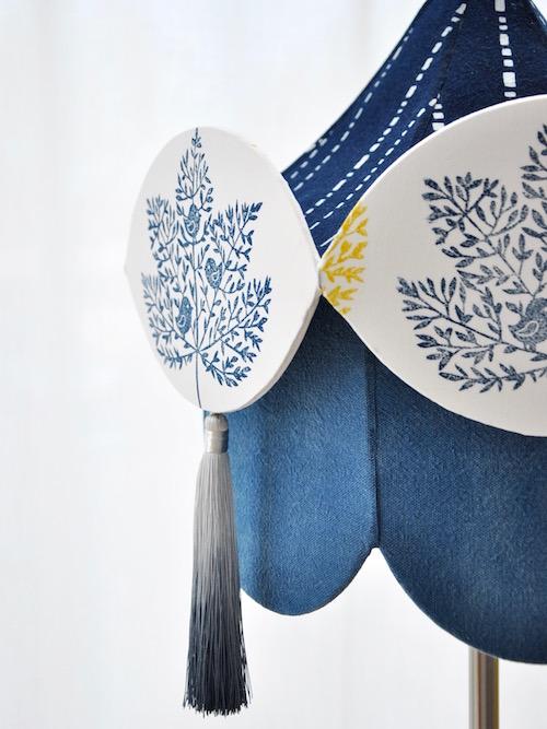 Abat-jour carrousel couleur bleu indigo, motif imprimé à la main sur du coton biologique, décoré avec des pompons couleurs dégradées grises. Pièce unique originale créé par artisan d'art de France Inkrée.